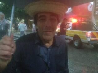 Ex-deputado Adriano Diogo Faria se protege da chuva durante ato da CUT