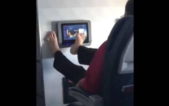 O passageiro usando o tablet com os pés causou reações de repulsa dentre mais de 9 milhões de usuários do Twitter