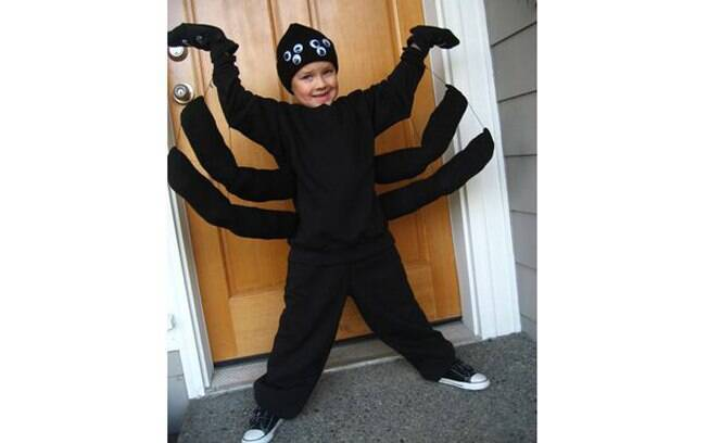 Os bracinhos costurados na camiseta preta e a touca de lã com apliques de olhos de brinquedo montam uma fantasia divertida de aranha