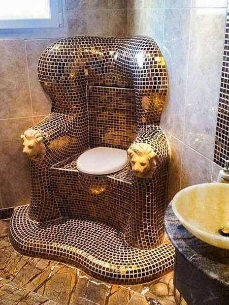 Banheiro decorado com mármore e um trono no lugar do vaso sanitário