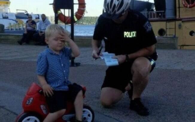 O pequeno Declan Tramley leva a mão ao rosto ao ser abordado por agente canadense