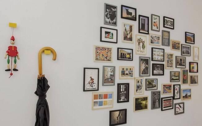 Os ganchos em metal amarelo dão graça à parede, na mistura com os quadros