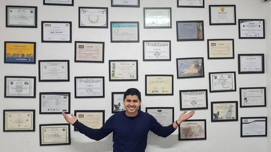 Cleber Santos a frente de seus diplomas, todos cursos voltados para área pet