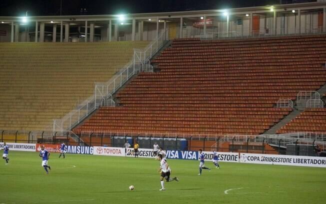 O zagueiro Paulo André domina a bola, tendo  ao fundo a visão das arquibancadas vazias do  Pacaembu