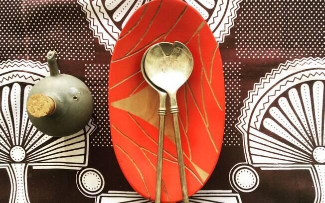 E que tal caprichar na montagem da mesa de jantar? Linda essa mistura de estampas do tecido com a peça vermelha em madeira pintada à mão
