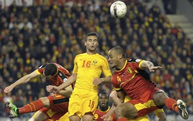 Jogadores de Macedônia e Bélgica brigam pela  bola. Os belgas venceram por 1 a 0