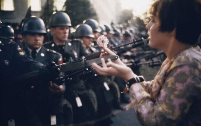 Jan Rose Kasmir, de 17 anos, entrega uma flor para um soldado durante uma manifestação contra a guerra em frente ao Pentágono, nos EUA, 1967.