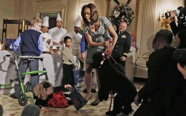 Michelle Obama reage depois de Ashtyn Gardner perder o equilíbrio ao ser cumprimentada pelo cachorro Sunny (4/12/2013)