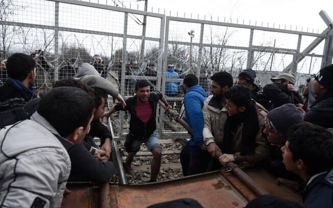 Refugiados quebram uma cerca de arame farpado na fronteira entre a Macedônia e a Grécia