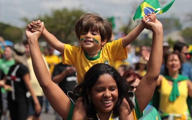 Mãe e filho participam de protesto vestido verde e amarelo em Brasília neste domingo dia 15 de março. Foto: AP Photo/Eraldo Peres