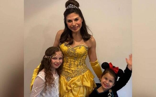 Mãe, fantasiada de princesa da disney, junto com as duas filhas, que também se fantasiaram.