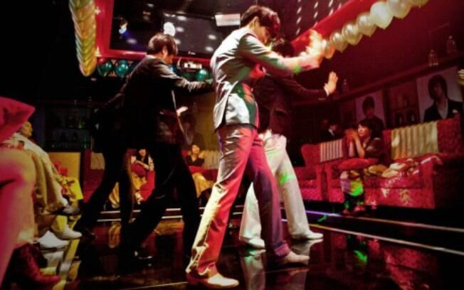 Rapazes dançam e tentam chamar a atenção das clientes em bar da Coréia do Sul