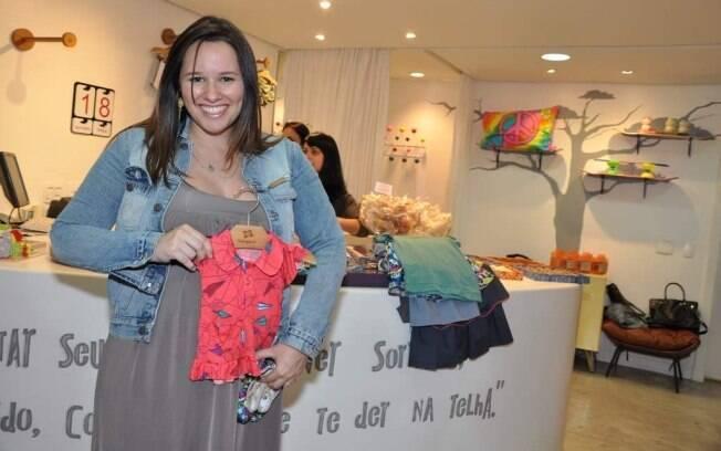 Grávida de seis meses e meio, Mariana Belém segura o vestidinho para a chegada de sua primeira filha, Laura