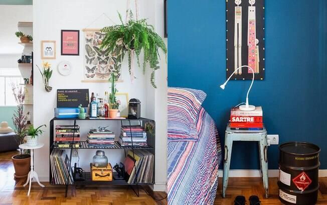 Livros bem distribuídos, misturados com os vinis, bandeja e plantas criam um cantinho interessante na casa. Já no quarto, o banco serve como cabeceira