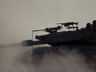 An Israeli tank takes a position along the Israel-Gaza Border, Thursday, July 17, 2014. Israel and Hamas have begun observing a five-hour humanitarian cease-fire, as fighting extended into a 10th day. The two sides agreed to the pause following a request by the United Nations so that supplies could be delivered to Gaza.(AP Photo/Ariel Schalit)