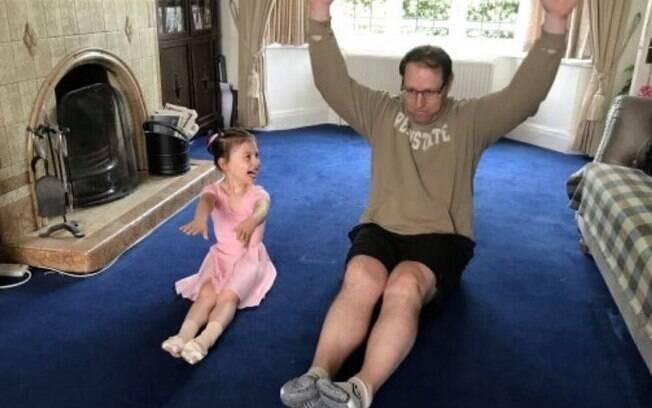 Pai com a filha tendo uma aula de balé juntos