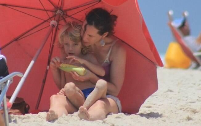 Ela protege Gael do sol enquanto ele come milho