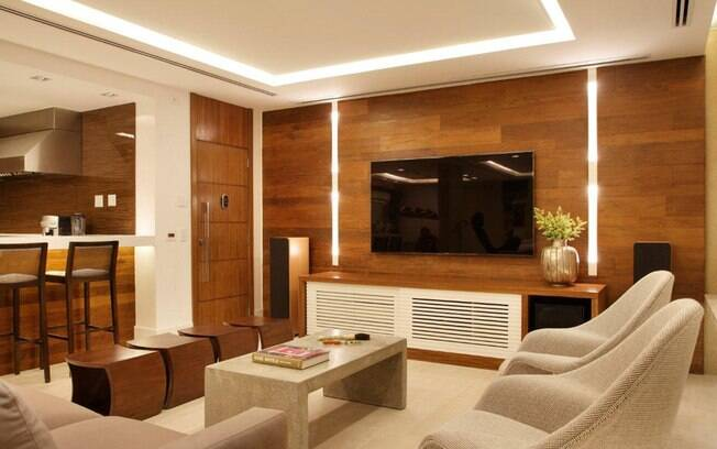 É a iluminação bem pensada que possibilita a integração de home theater e cozinha neste apartamento de Bianca da Hora