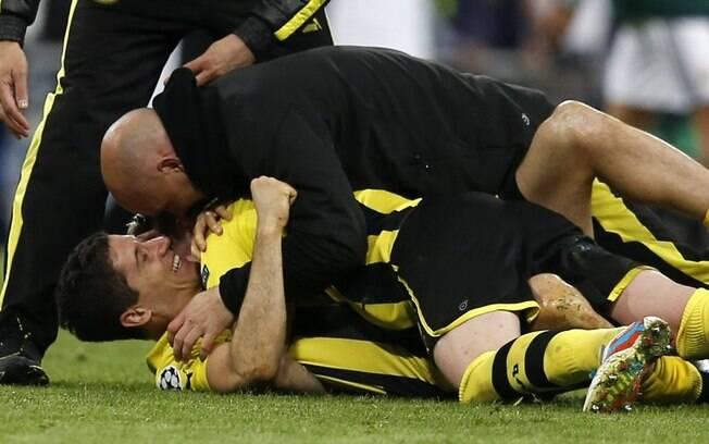O atacante Lewandowiski é abraçado pelos  companheiros após a classificação do Borussia, que  veio mesmo após a derrota diante do Real
