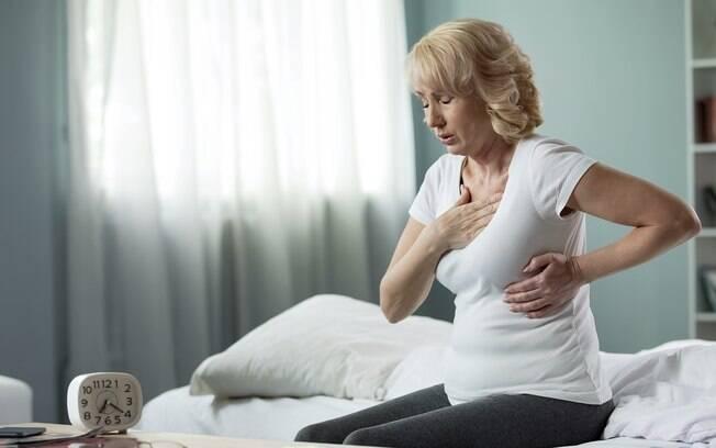 Mulher sentada na cama com a mão sobre o peito, sentindo dores