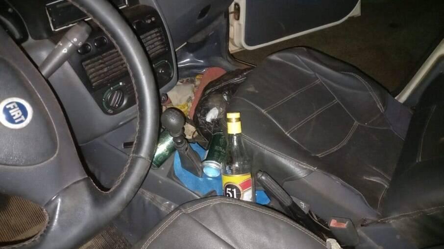 Polícia vasculha dentro de carro do homem, latas e garrafas de bebidas alcoólicas são encontradas