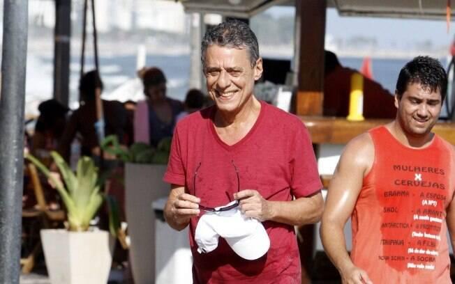 Chico Buarque sorri para fotógrafos após deixar praia e atender pedido de fãs