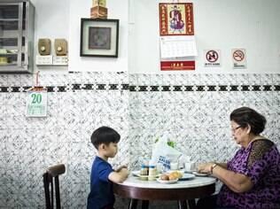 Mulher e seu neto tomam um tradicional café da manhã em Cingapura, com ovos moles, torrada e café no  kopitiam Chin Mee Chin Confectionery