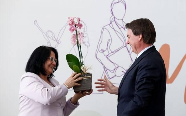 Ministra Damares Alves recebe flor em evento do Dia Internacional da Mulher com o presidente Jair Bolsonaro