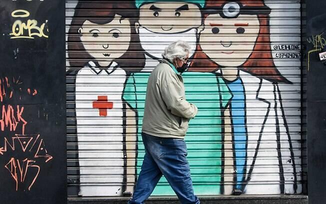 Idoso com máscara devido a Covid-19, caminha em frente a um grafite de médicos e enfermeira pintado na porta de uma loja fechada