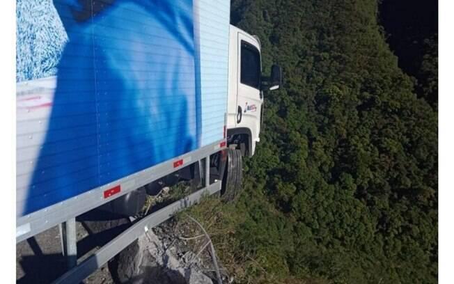 O caminhão ficou pendurado na mureta de proteção da rodovia