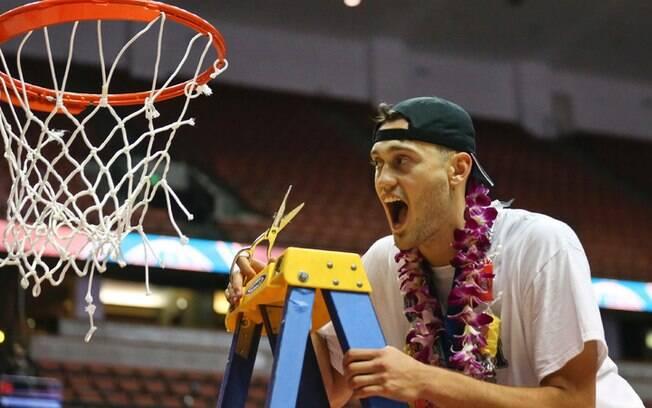 Após ser campeão, jogador corta a rede da cesta de basquete