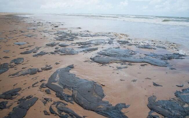 Manchas de óleo na areia de uma praia no Nordeste
