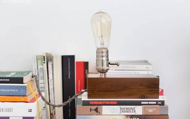 A luminária sobre os livros faz uma ocupação interessante e fácil para a cabeceira
