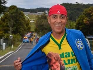 Vestido a caráter, pai de David Luiz faz visita ao filho na Granja Comary