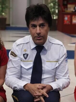 Tom Cavalcante como Gildo, o chefe de segurança do shopping aonde acontece a série