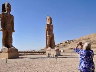 Turista tira foto de duas estátuas colossais do Faraó em 14 de dezembro de 2014
