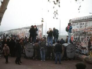 MUNDO - 07.11.2014 O Muro de Berlim foi um dos simbolos  da divisao do mundo entre socialistas e capitalistas nos anos da Guerra Fria . Ja sua queda , que completa 25 anos no proximo domingo (9) , foi a maior representacao da derrocada da Uniao Sovietica . Na foto , cidadaos alemaes ocidentais se reunem em uma abertura no Muro de Berlim , na Potsdamer Platz , em novembro de 1989 .  FOTO : Jim Garamone / U.S. Department of Defense