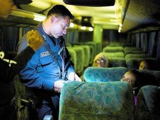 Segurança. Policial questiona mulher sobre os documentos de uma criança pequena que a acompanha para área próxima a fronteira