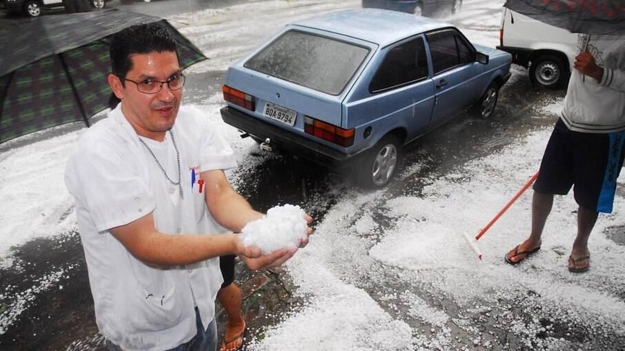 Homem mostra pedras de gelo que se acumularam em rua de Guarulhos, em São Paulo