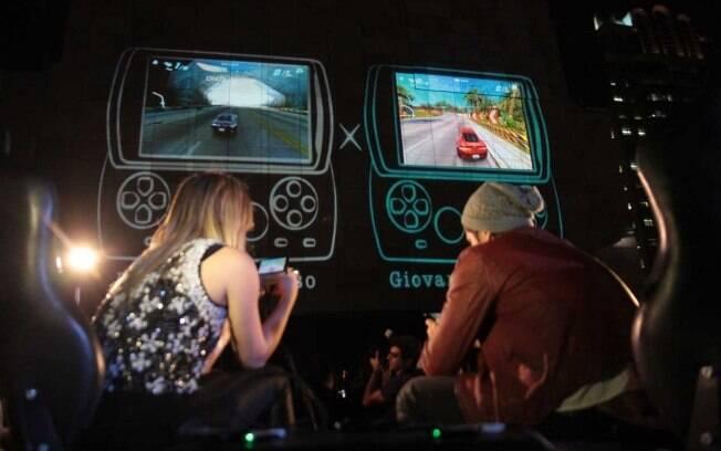 Enquanto o casal Bruno Gagliasso e Giovanna Ewbank disputa corrida virtual pelo celular a imagem é exibida no telão