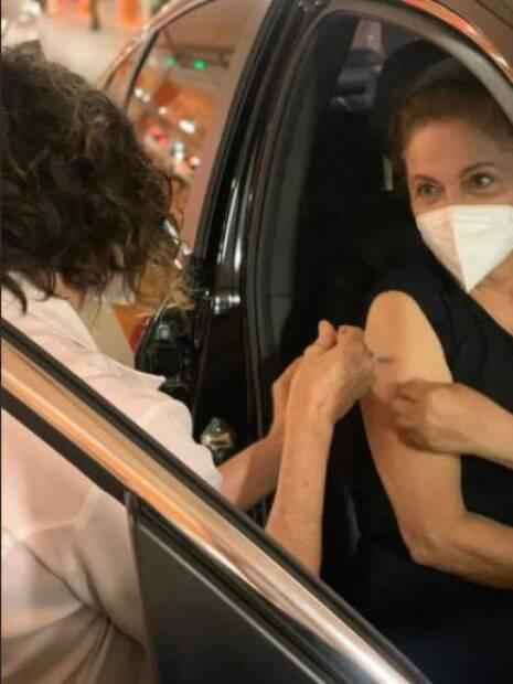 Dilma dentro de carro sendo vacinada no braço direito pela janela