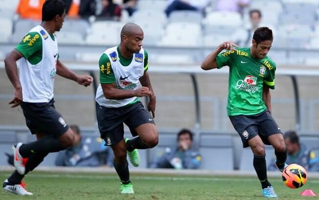 Neymar domina a bola durante o treino da  seleção brasileira, diante da marcação de  Fernando