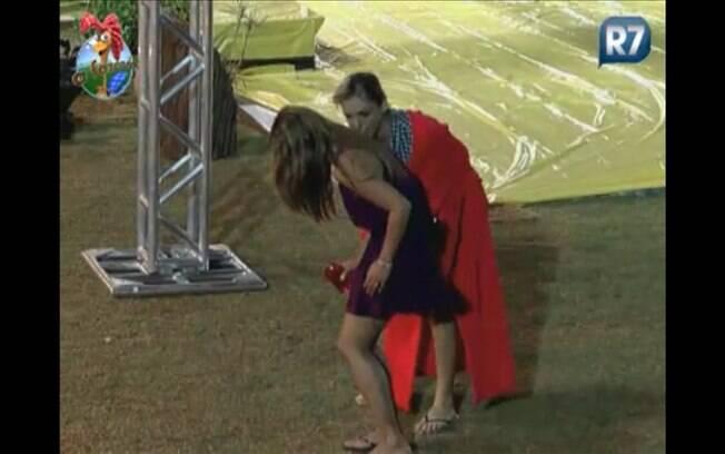 Anna ajuda a amarrar a parte debaixo do biquini de Raquel