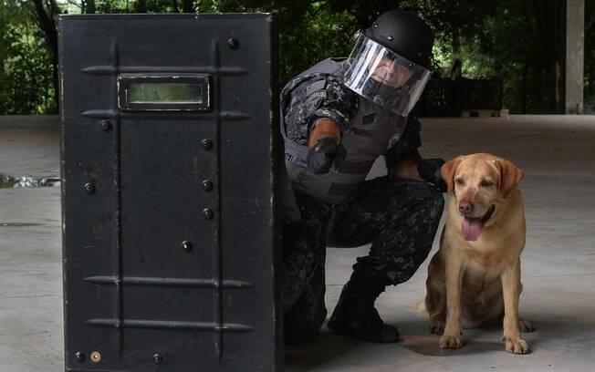 Cabo Alves, parceiro de Marley, indica para cão a localizacao para faro de explosivo