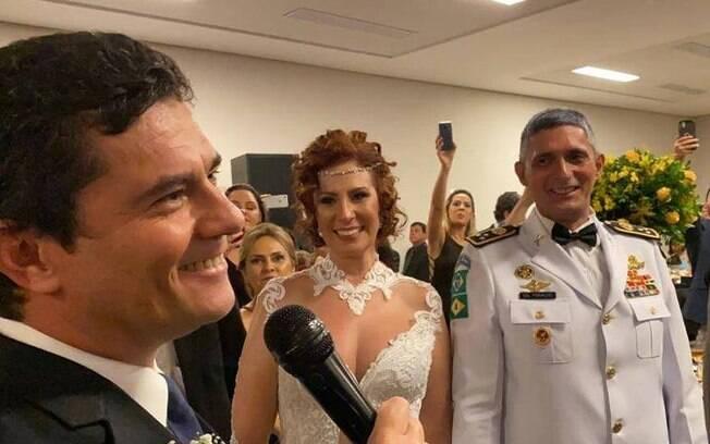 homem sorrindo e mulher vestida de noiva atrás dele