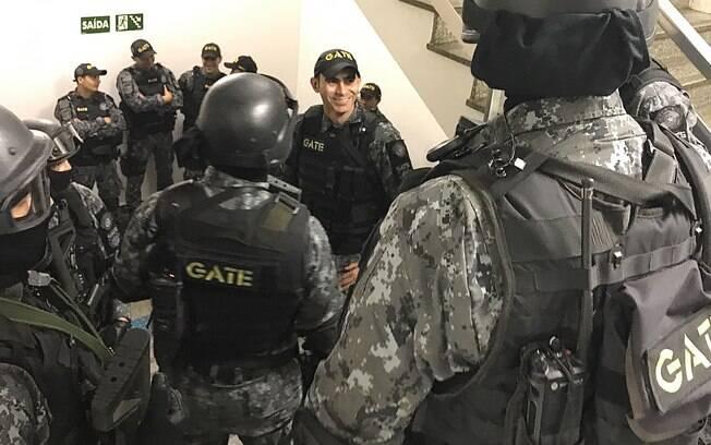 Na escadaria da Câmara Municipal, ao lado da área a ser invadida, o Capitão PM Wellington (centro) repassa os detalhes da ação para a Equipe de Invasão Tática (de capacete). Ao fundo e em baixo, de boné, estão alguns membros do Esquadrão Antibomba
