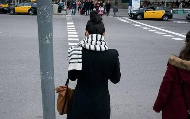Moça esperando pra atravessar a rua