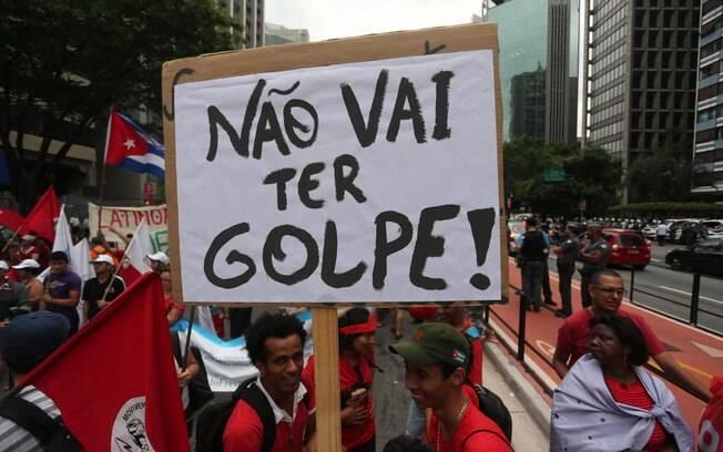 Manifestantes levam placas com os dizeres