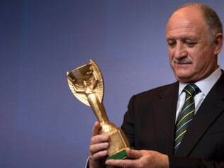 Brazil's soccer coach Luiz Felipe Scolari holds a replica of the 1970's World Cup trophy handed by a fan at the end of a press conference where he announced his list of players for the Confederations Cup in Rio de Janeiro, Brazil, Tuesday, May 14, 2013. (AP Photo/Felipe Dana)