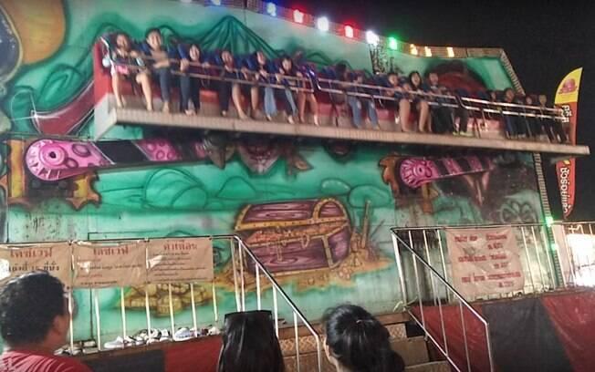 Crianças em brinquedo em parque de diversões na Tailândia